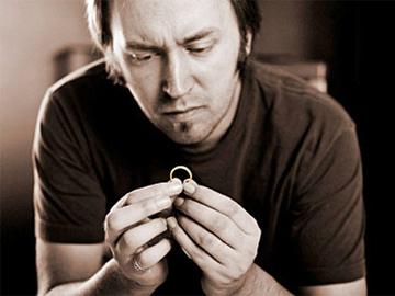 мужчина держит обручальное кольцо, жизнь после развода